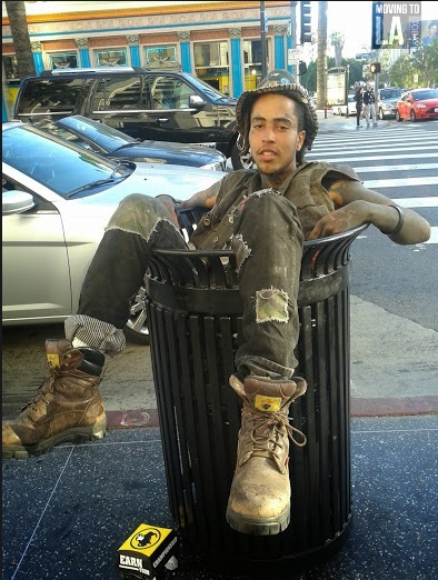Man sitting in trash can. I think he was faking being homeless.